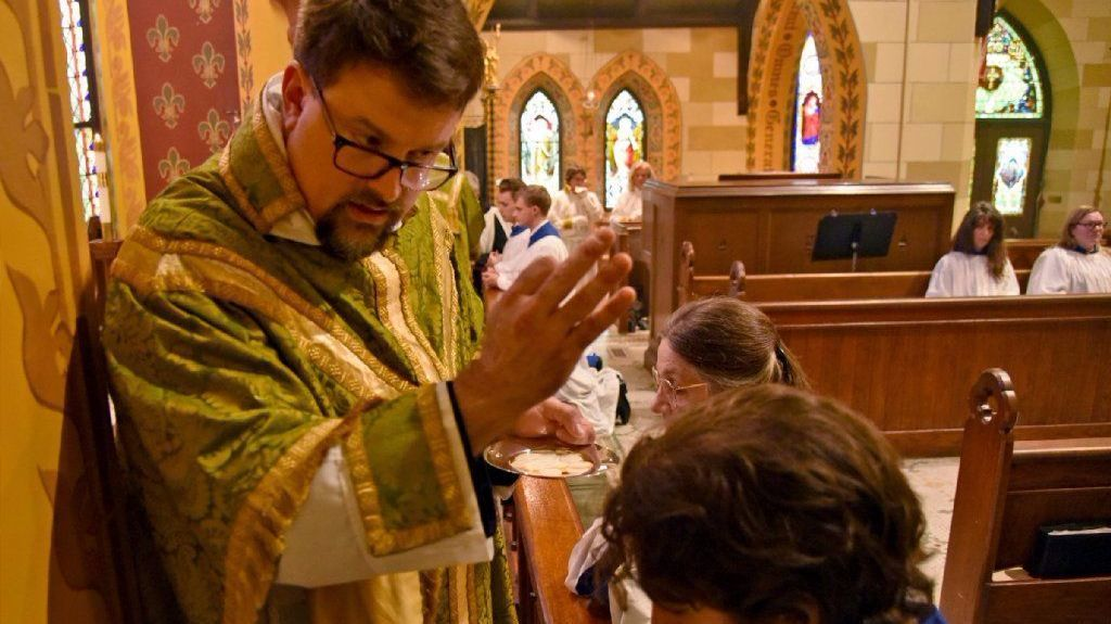 Rev. Jeffrey C. Hual, known as Father Hual, offers blessings during communion at St. John's Episcopal Church in the Village.