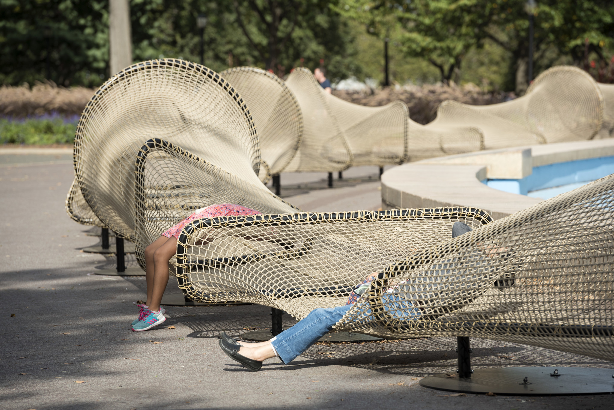 "Visitors recline on the netting of ""Circle Fence."""