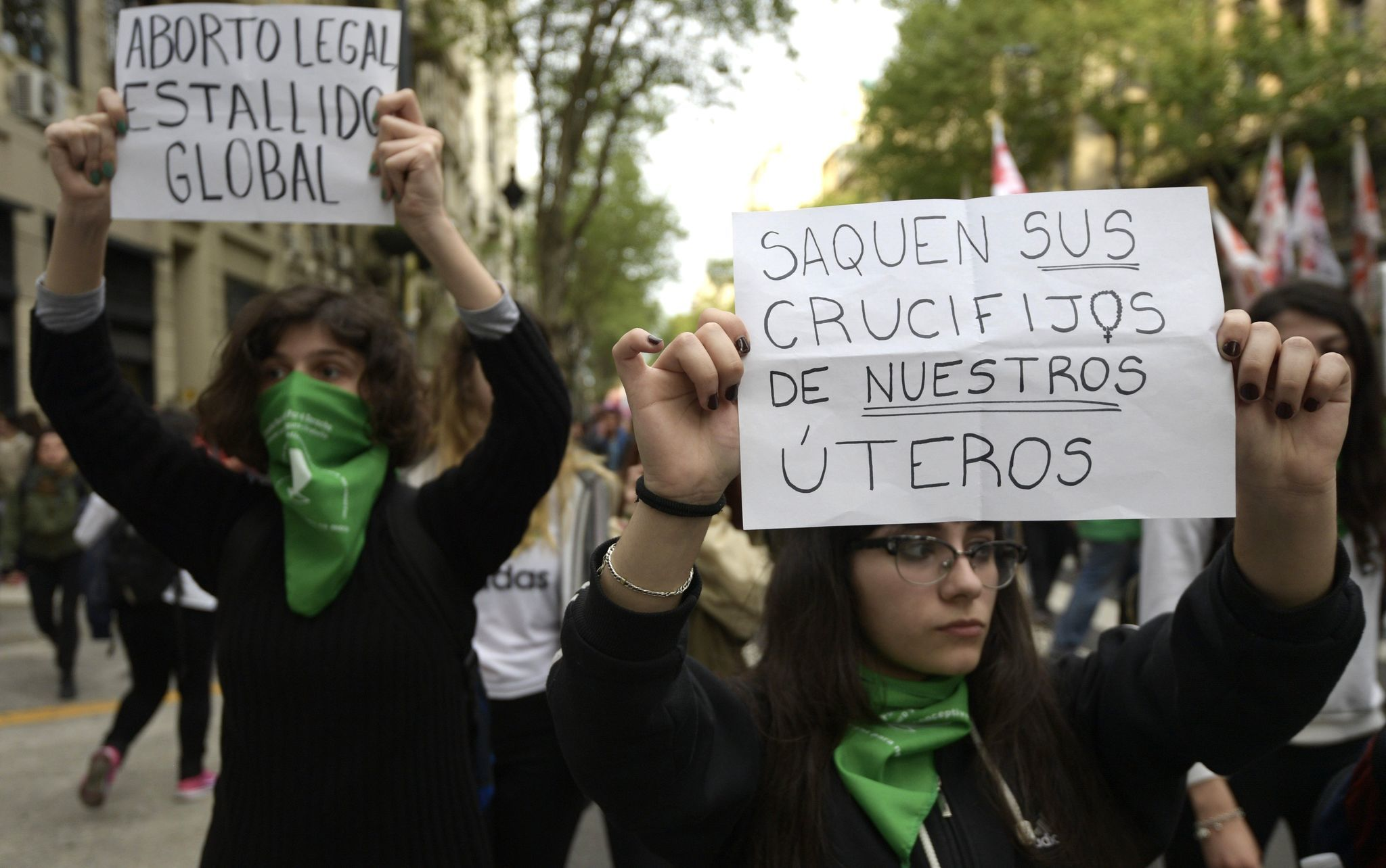"Women hold signs reading ""Legal abortion, global outbreak"" (L) and ""Take your crucifixes from our wombs"" during a September protest demanding the decriminalization of abortion in Buenos Aires."