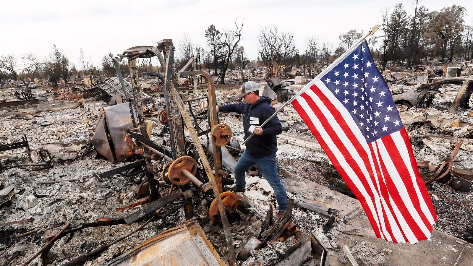 Jason Miller, 45, plants an American flag on the charred remains of his house in Coffey Park. He had lived in the Santa Rosa neighborhood for 23 years. (Luis Sinco / Los Angeles Times)