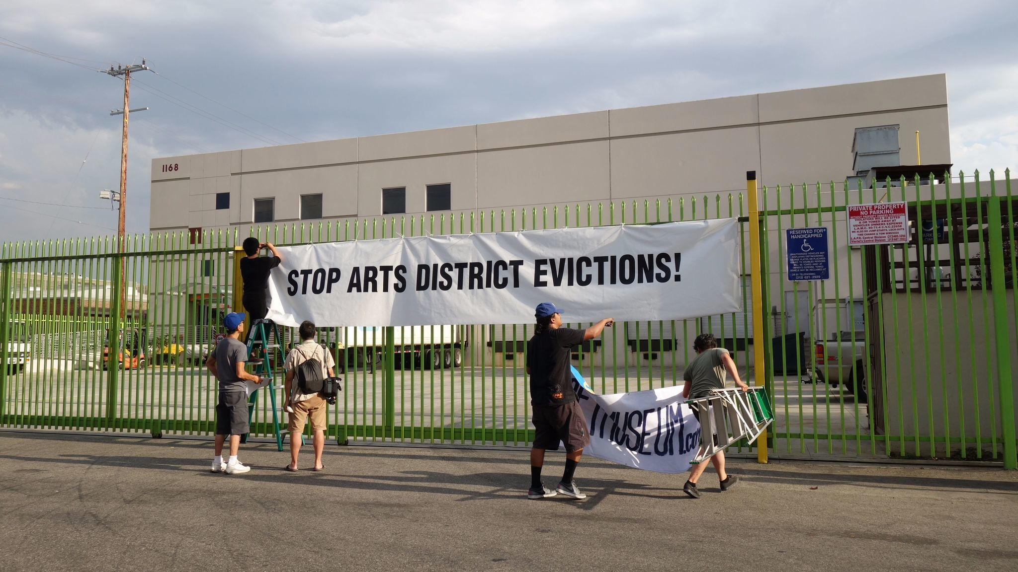 Artists place a sign protesting evictions in the Arts District outside of Seaton Street lofts.