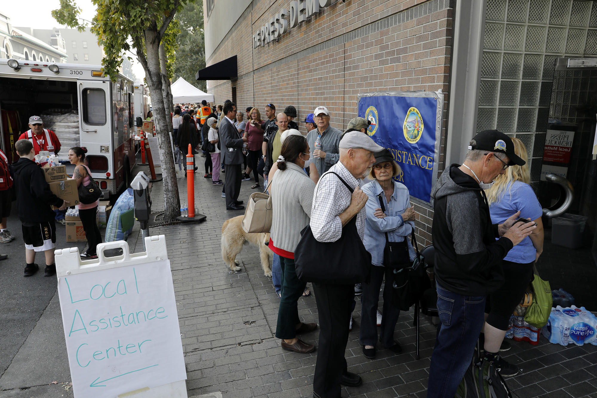 People line up outside an assistance center set up at the Santa Rosa Press Democrat building.