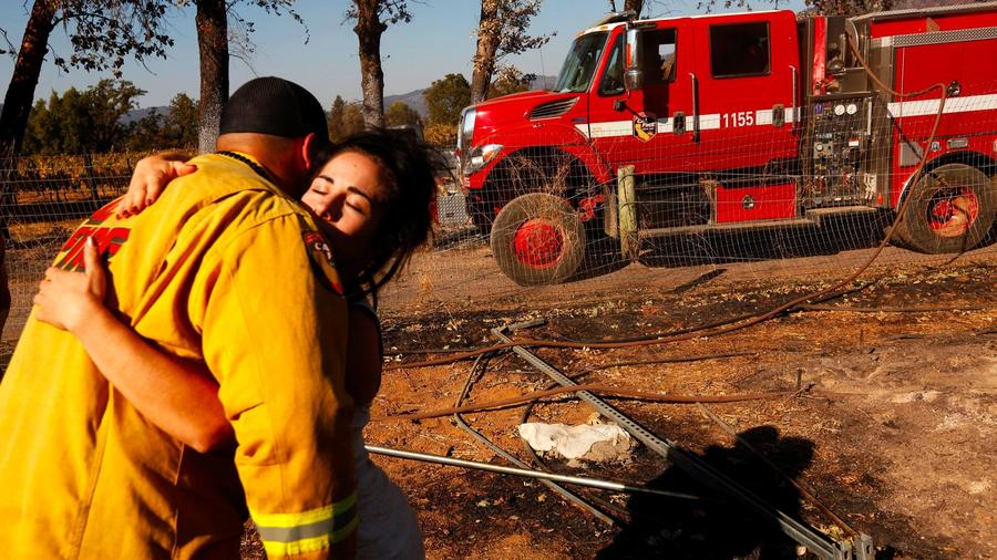 Ashley Oldham, owner of Frost Flower Farms, hugs a firefighter who was putting out hot spots at her marijuana farm in Redwood Valley. — Photograph: Genaro Molina/Los Angeles Times.