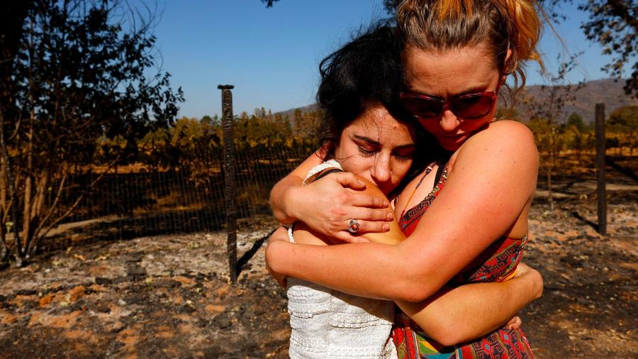 Ashley Oldham, owner of Frost Flower Farms, left, receives a hug of support from friend Serena Inda in Redwood Valley. — Photograph: Genaro Molina/Los Angeles Times.