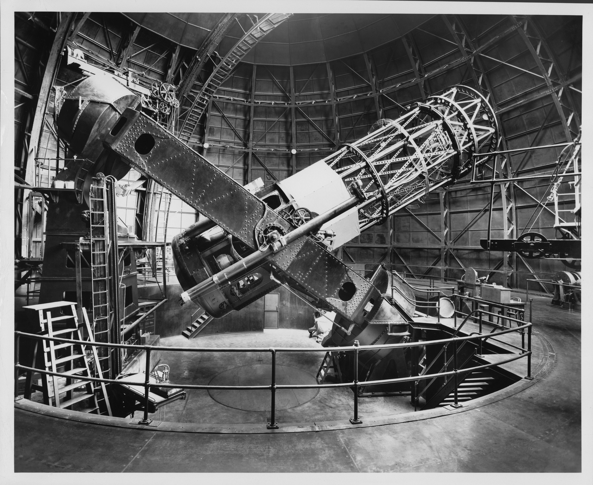 The Hooker 100-inch reflecting telescope, side view with tube 40 degrees from horizontal. Edwin Hubble's chair, on an elevating platform, is visible at left.