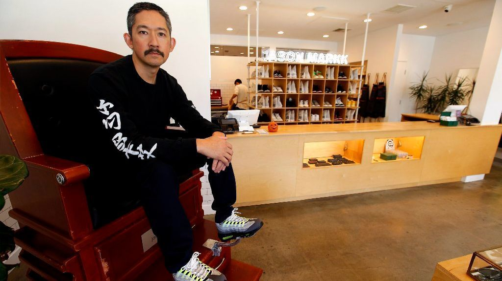 "Jason Mark Angsuvarn of Jason Markk sits on the ""JM Throne,"" a shoe shine chair on display at the company's flagship store in Little Tokyo."