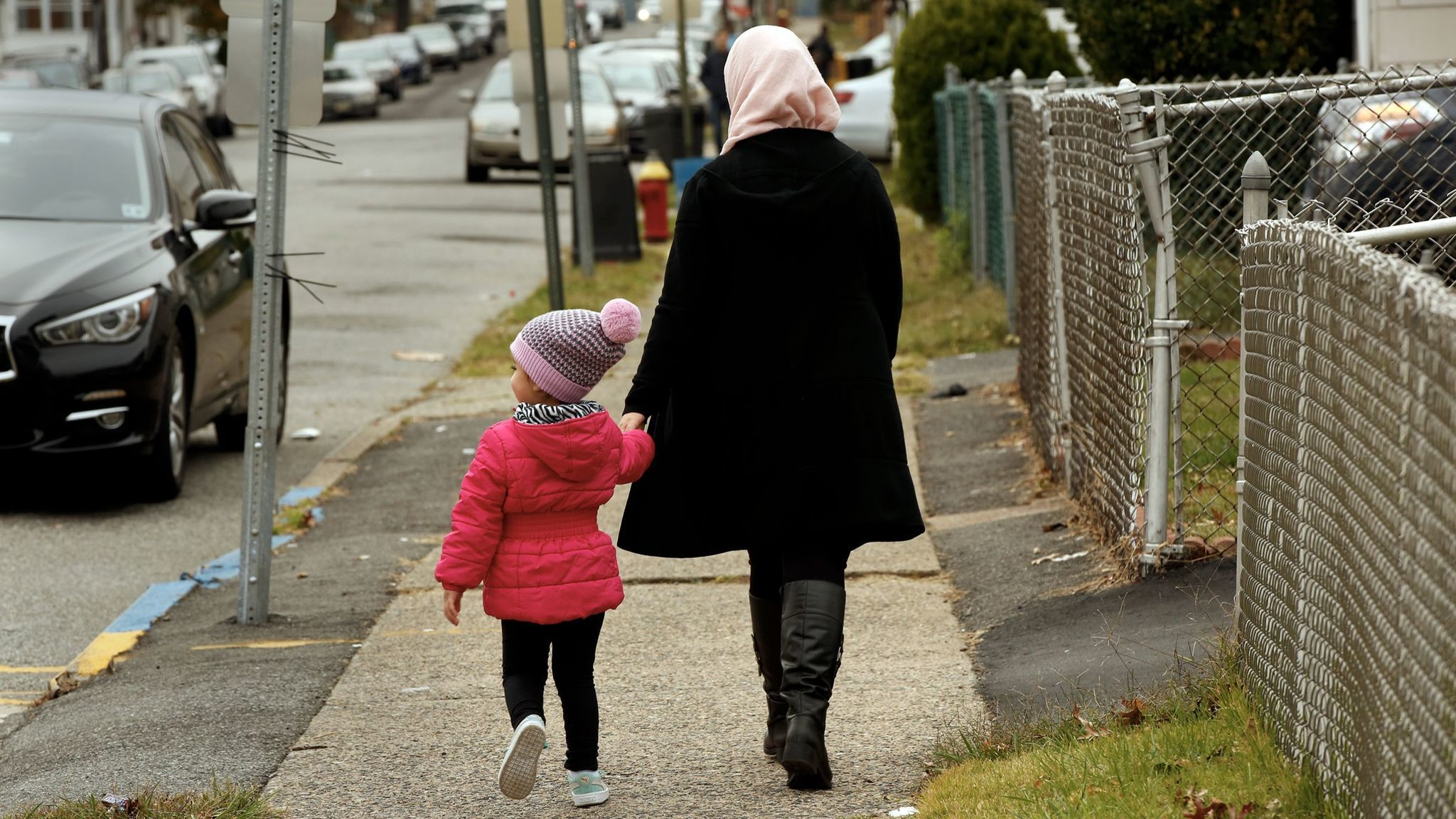 A woman walks with her child on the street where Sayfullo Saipov lived.