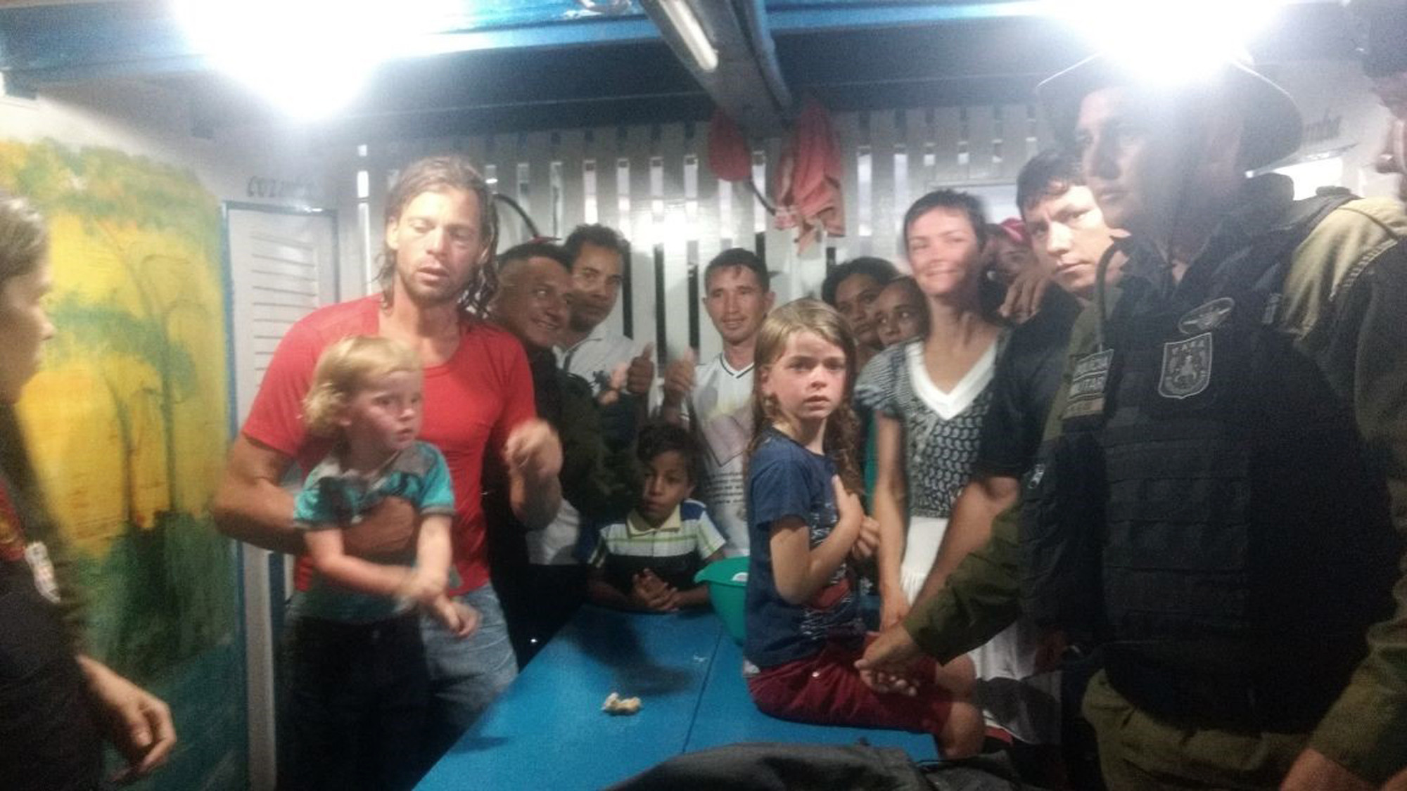 This Nov. 1 photo provided by Brazilian officials shows Adam Harteau, left, Emily Harteau, third from right, and their two daughters with police and Brazilian villagers after the family's rescue.