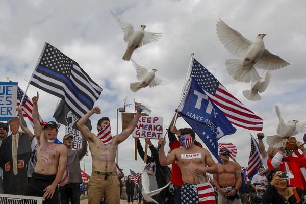 White doves are released at the start of a Pro-Trump march, organized by Make America Great Again, in Huntington Beach, Calif. on March 25. (Los Angeles Times)