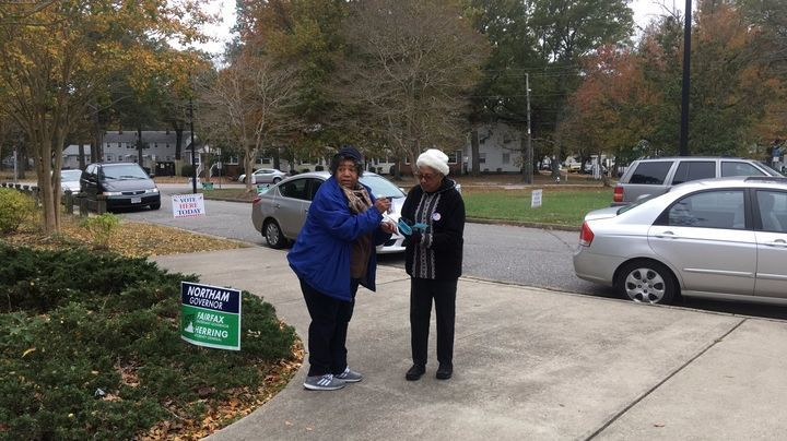 From left, Democratic Party volunteers Renee Lovett and JoAnn Wray, hand out flyers in front of Achievable Dream Middle and High School.