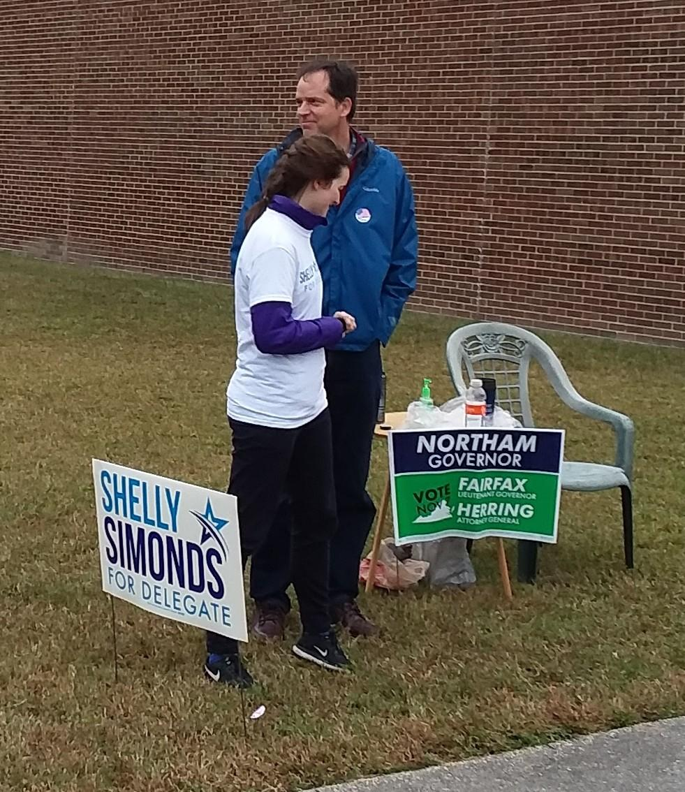 Democratic House of Delegates candidate Shelly Simonds' husband and daughter are greeting voters at the Watkins precinct in Newport News.