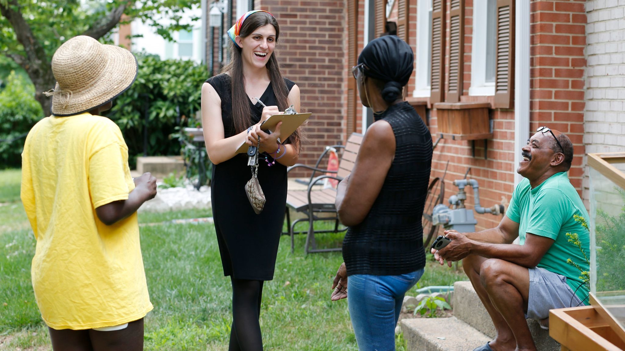Danica Roem, second from left, talks with voters as she canvasses a Manassas, Va., neighborhood in June.
