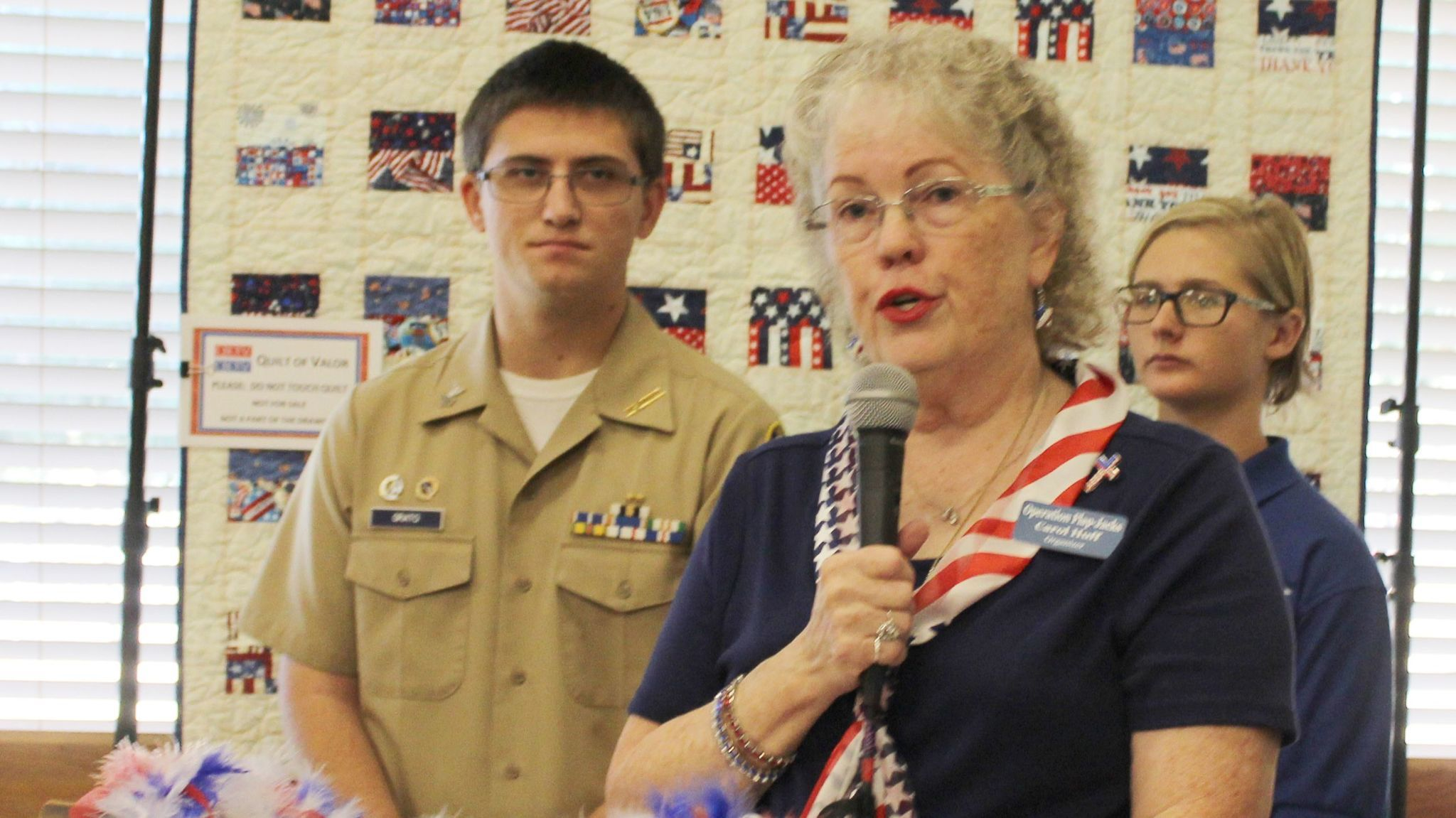 With the World War II veteran Bill Brown's Quilt of Valor in the background and NJROTC cadets Michael Grato and Victoria Leonard listening, Carol Huff explains the Quilts of Valor program.