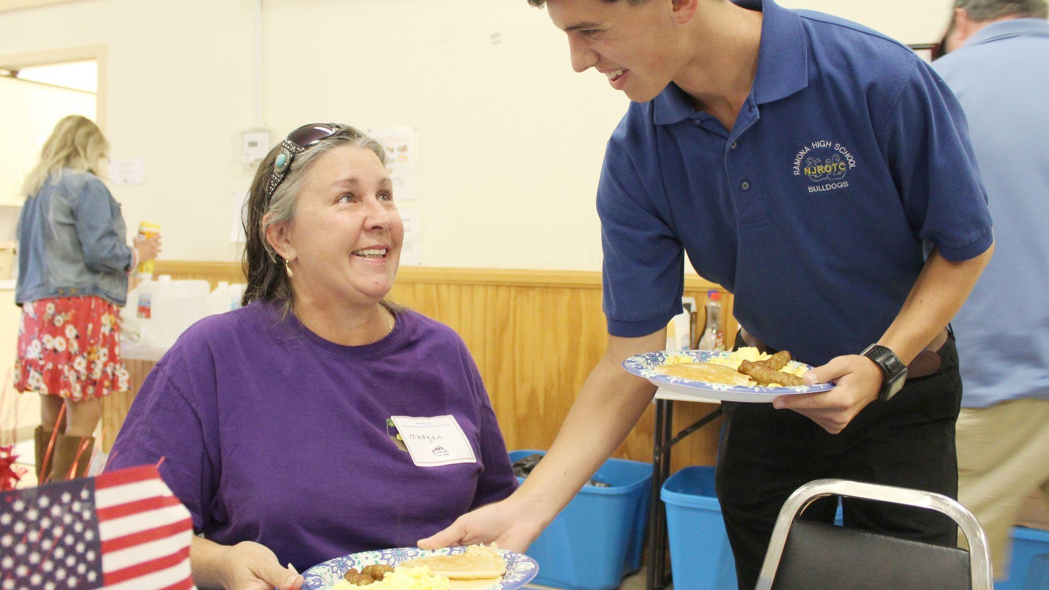 NJROTC Cadet Gavin Roche serves breakfast to Meagen Barrett and others at her table. Barrett is a Ramona Senior Center bus driver.