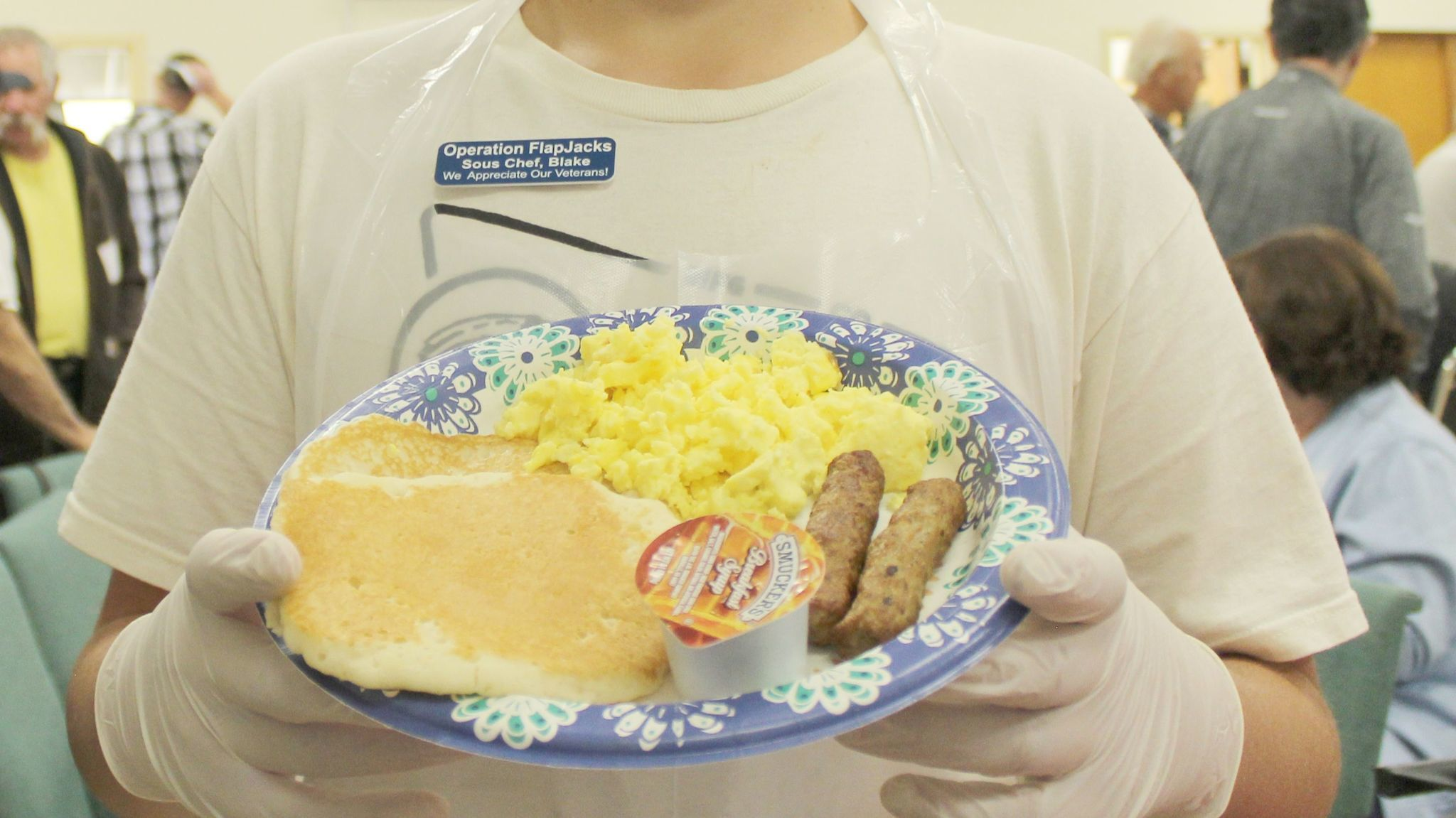 Volunteer Blake Yule, a Montecito High School sophomore, shows a plate of scrambled eggs, sausages and pancakes served at the breakfast.