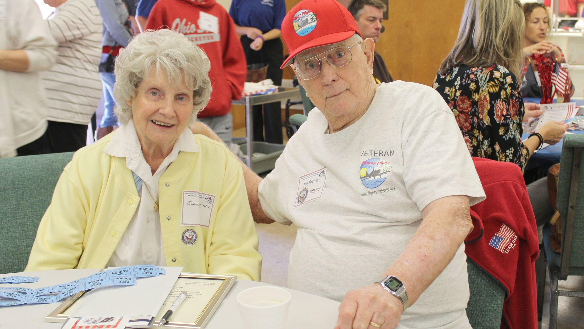 Wearing his Honor Flight T-shirt and cap, World War II Navy veteran Bill Brown sits with his wife Elly.