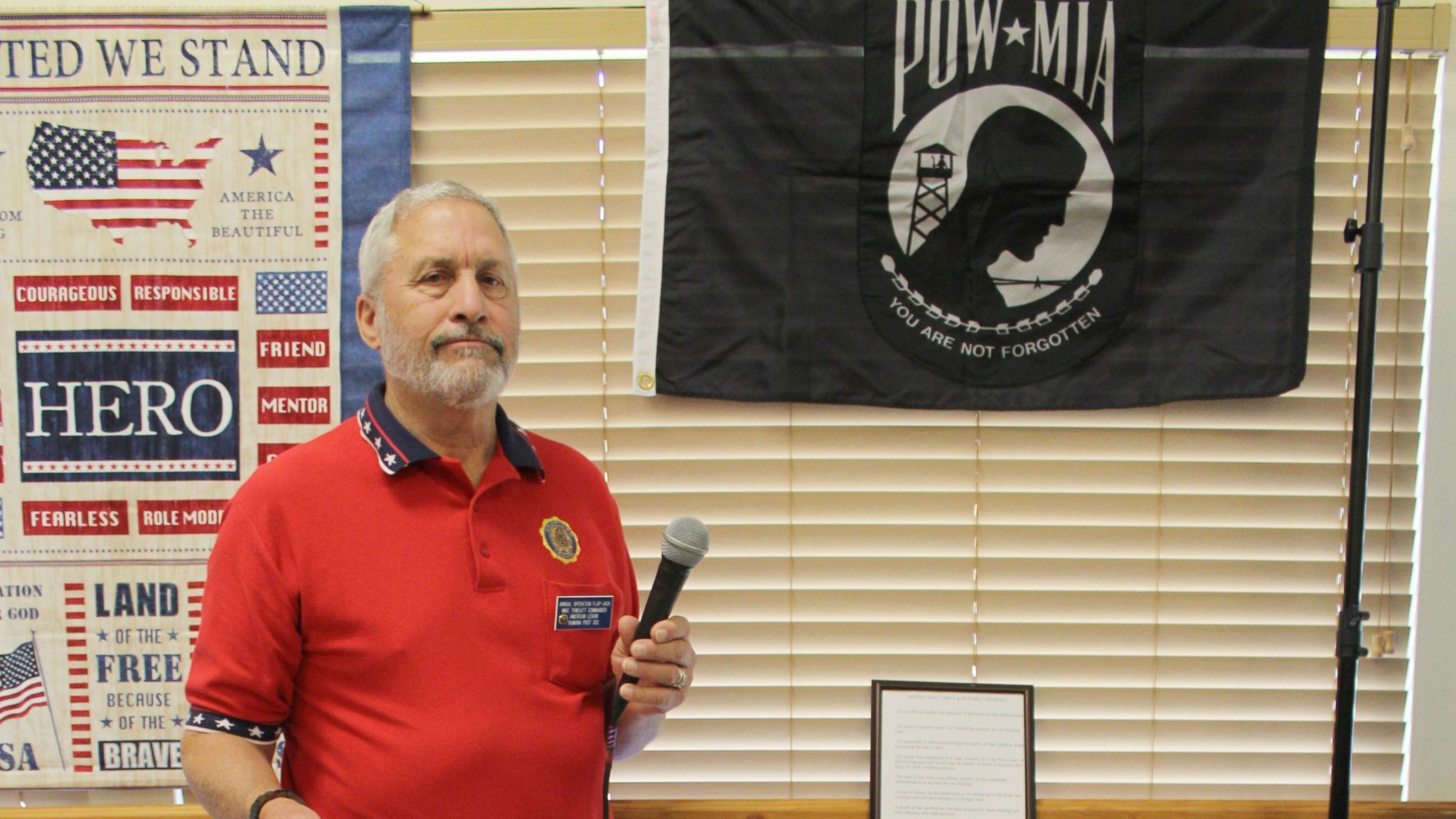American Legion Post 332 Cmdr. Michael Thweatt explains the meaning of the items on the Missing Man POW/MIA Table.