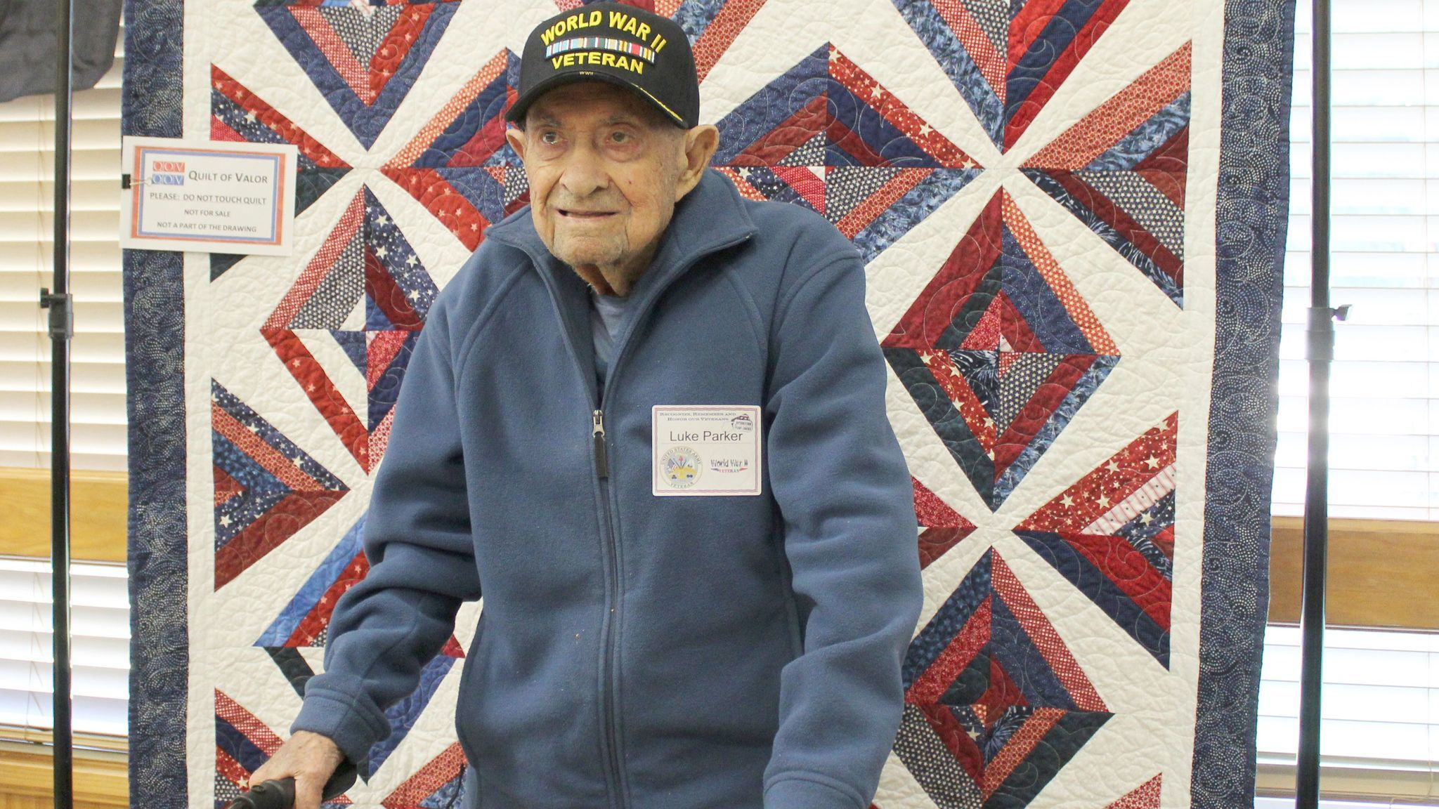 World War II Army veteran Luke Parker, 95, stands in front of his Quilt of Valor.