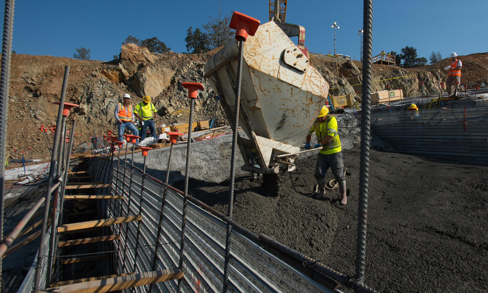 Leveling concrete is delivered from a large bucket attached to a crane on the lower chute of the Lake Oroville flood control spillway on July 14.