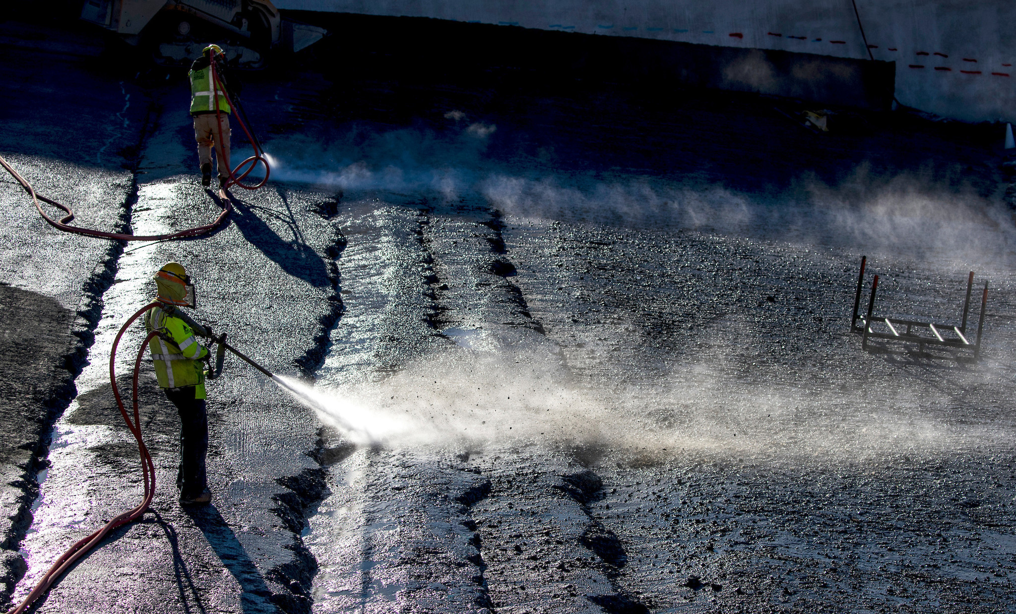 Workers use water and compressed air to remove loose rocks between the upper and lower chute in preparation for a layer of enriched roller-compacted concrete at the Lake Oroville flood control spillway on Oct. 25,