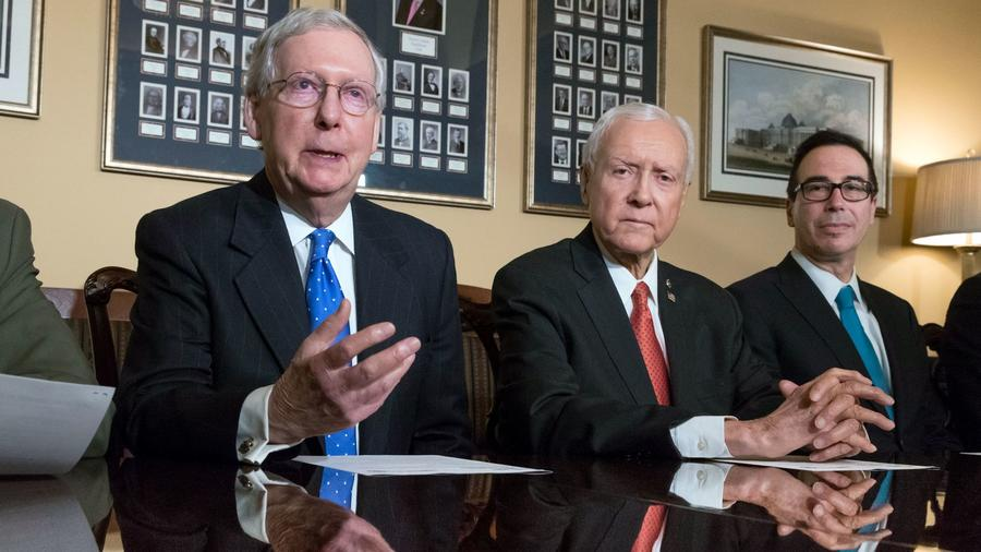 From left, Senate Majority Leader Mitch McConnell (R-Ky.), Senate Finance Committee Chairman Orrin Hatch (R-Utah) and Treasury Secretary Steven T. Mnuchin, talk about the Senate's tax bill at the Capitol. (J. Scott Applewhite / Associated Press) None