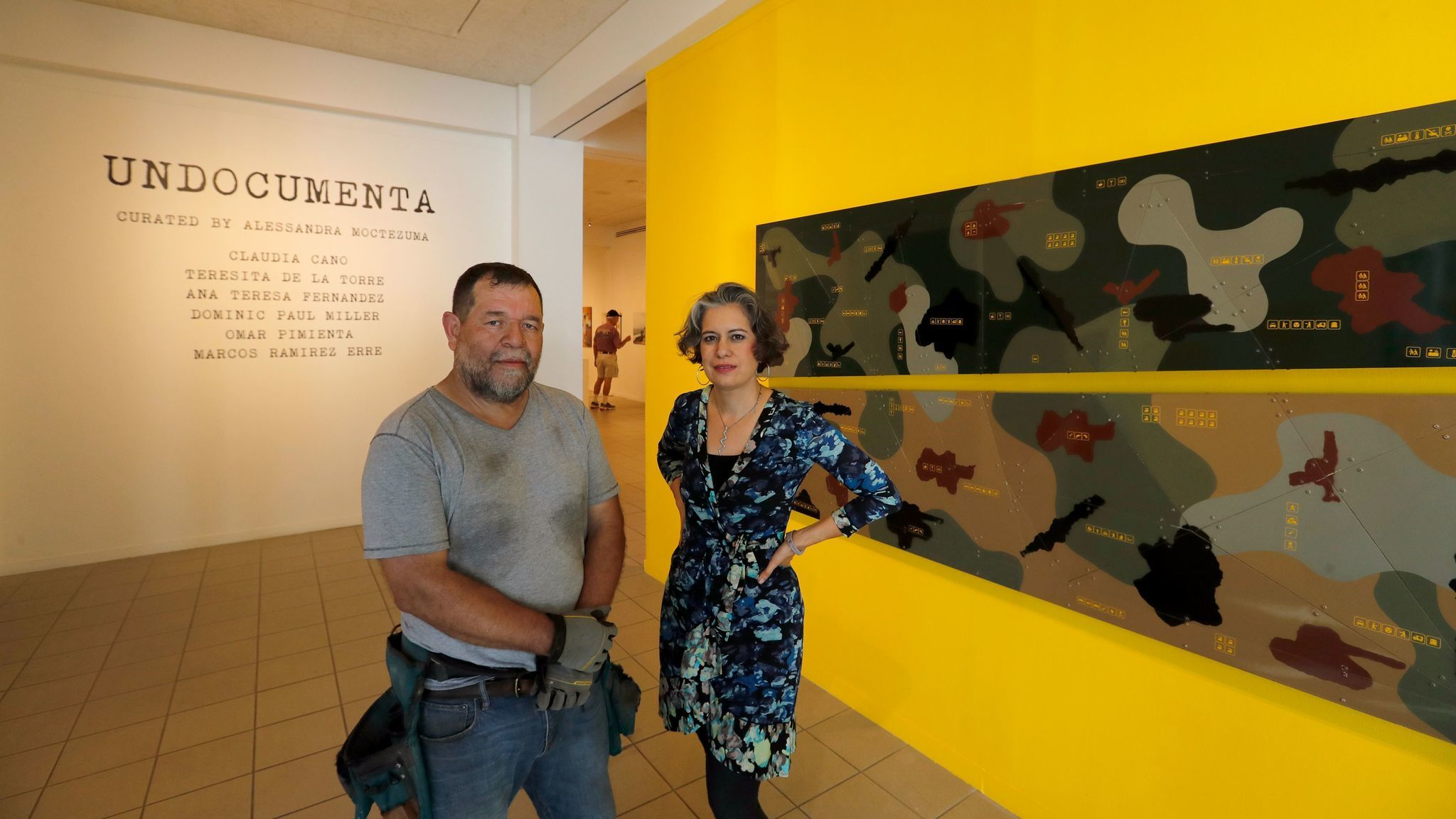 "Artist Marcos Ramirez ERRE and curator Alessandra Moctezuma stand before one of the artist's works in ""Undocumenta."""
