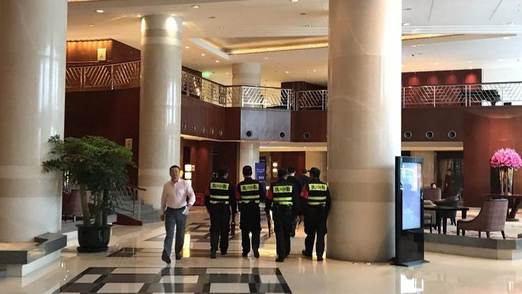 Security guards walk through the hotel in Hangzhou, China, where three UCLA basketball players are staying. (Gaochao Zhang / For The Times)