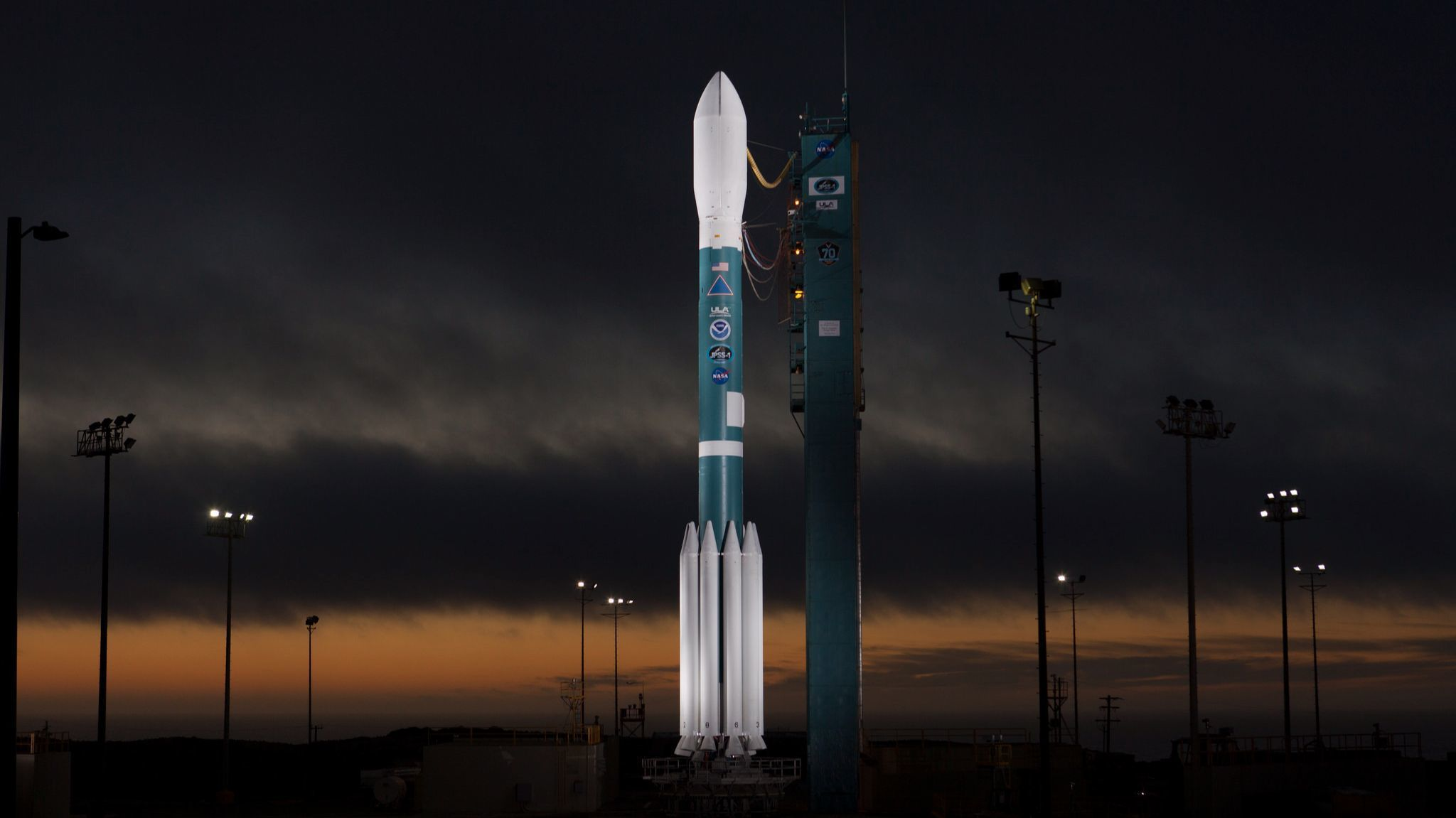 The Delta II rocket set to launch the JPSS-1 satellite is illuminated as night falls at Vandenberg Air Force Base. It is scheduled to launch early Wednesday.