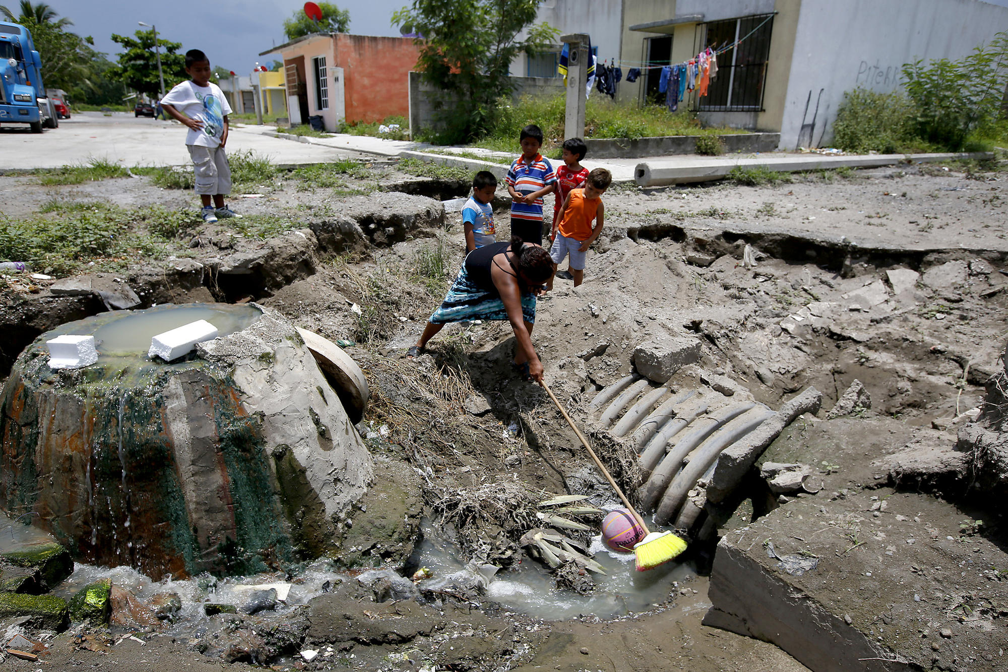 Adela Blanco uses a broom to retrieve a basketball from an open pit of raw sewage near her home in Colinas de Santa Fe in Veracruz, Mexico.