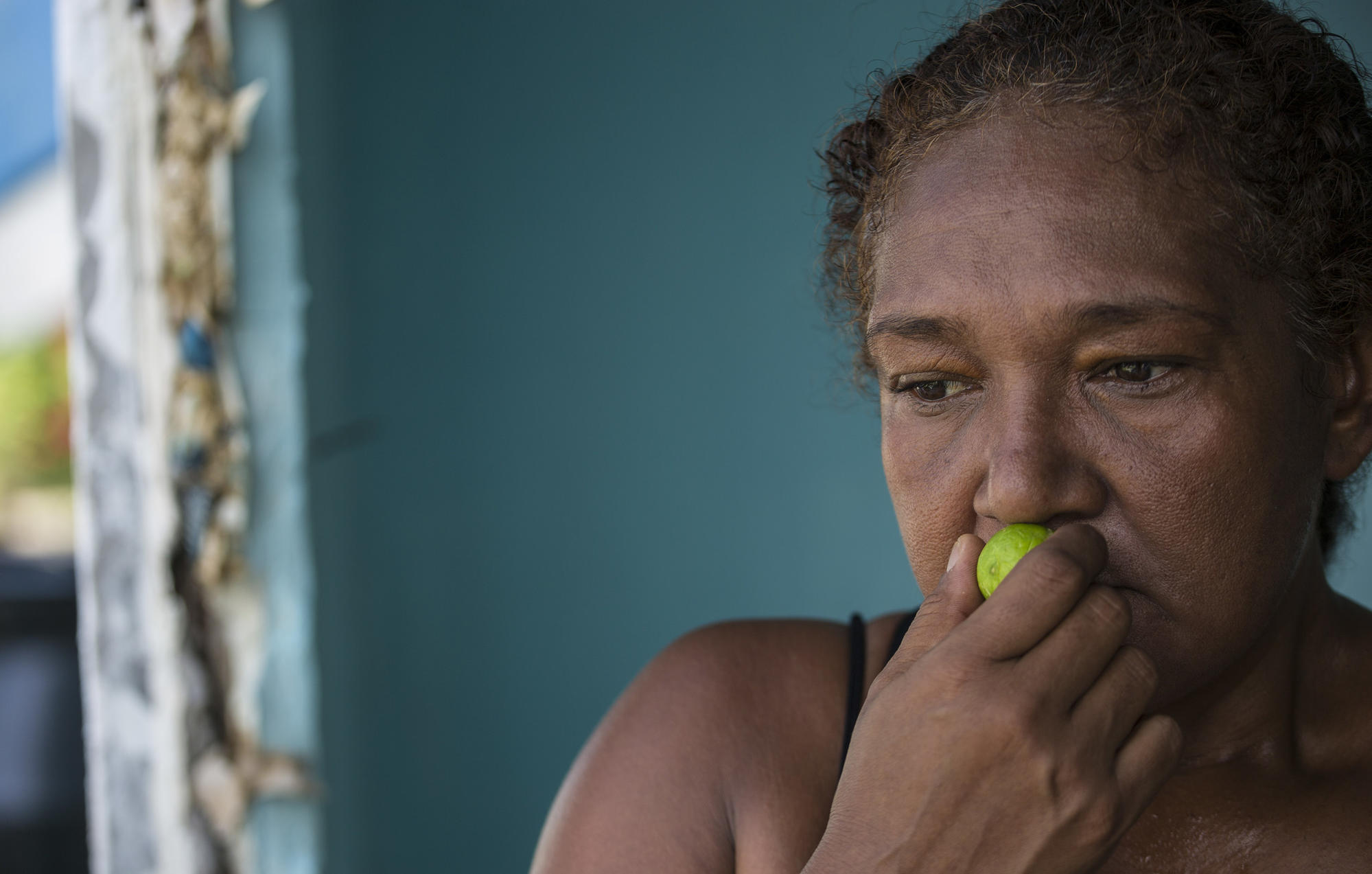 Adela Blanco, 47, holds a lime to her nose to mask the odor of raw sewage, which flows through the streets of the Colinas de Santa Fe development in Veracruz, Mexico.