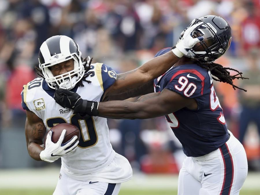 Rams running back Todd Gurley straight-arms Houston Texans linebacker/defensive end Jadeveon Clowney during a Nov. 12 game at the Coliseum. (John Cordes / Associated Press)