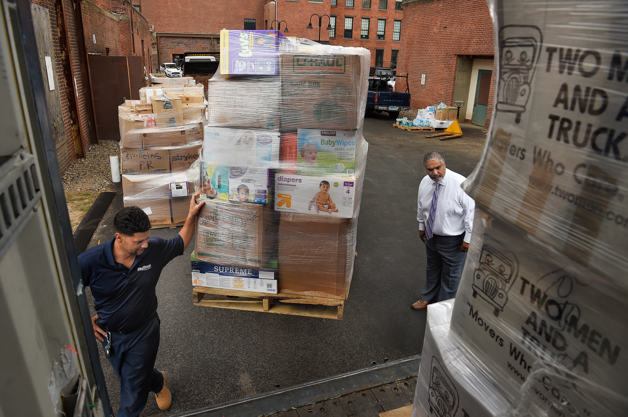 Jimmy Velasquez (left) guides a load of hurricane-relief supplies onto as shipping container as Elliot Matos watches near the Colt building in Hartford.