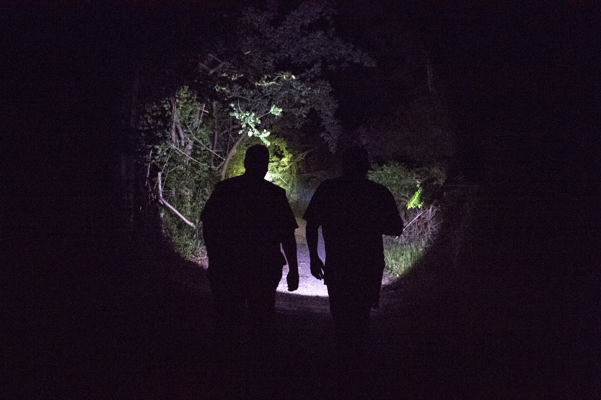 In San German, Puerto Rico, Elliot Matos, at left, and David Velasquez shine a spotlight to illuminate their path on a rural road as they search for an address in the dark, hilly terrain.
