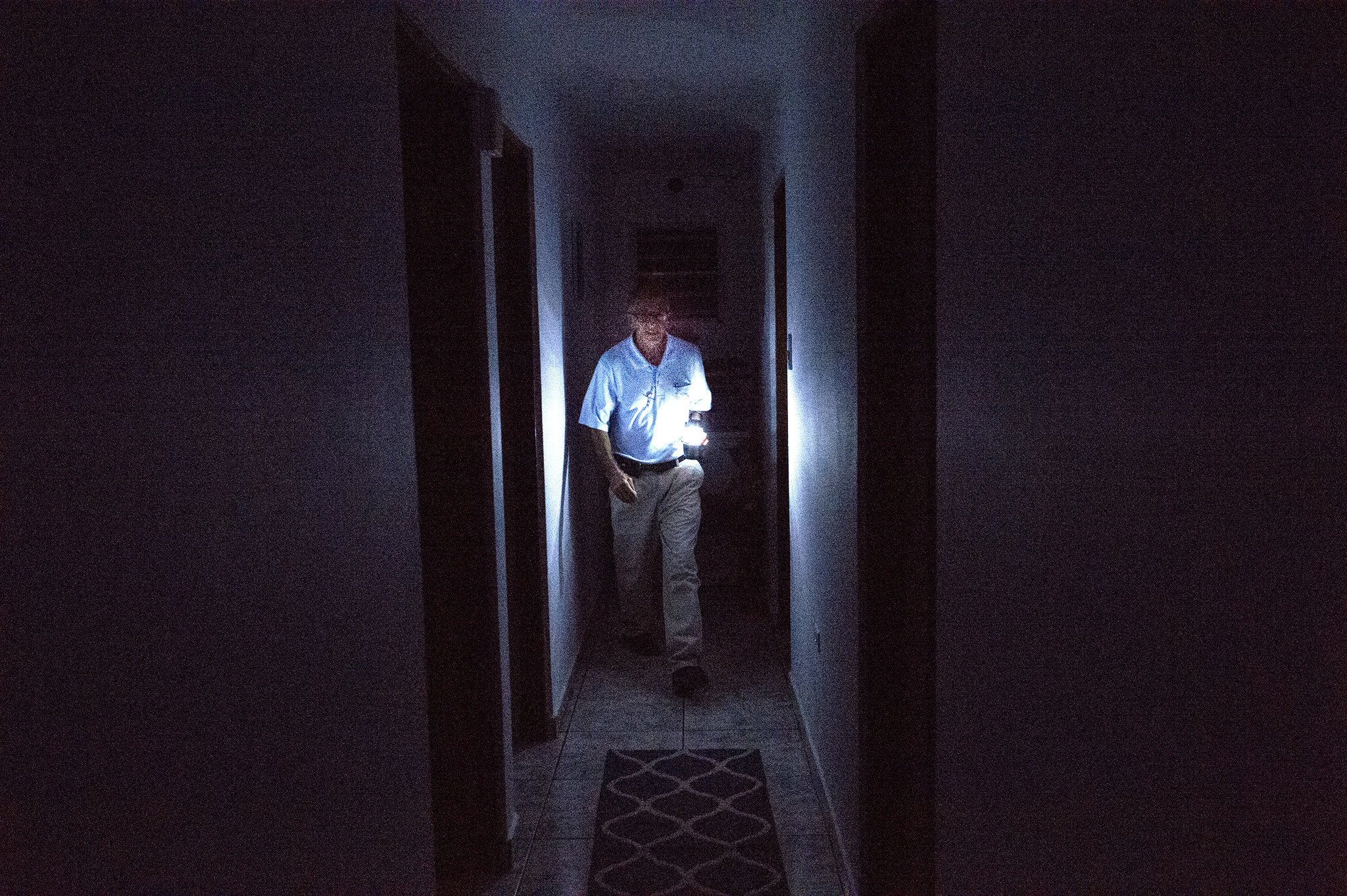David Morales, of Patillas, Puerto Rico, uses a solar lamp to navigate through his home. Many people in Puerto Rico like Morales are still without electricity and running water.