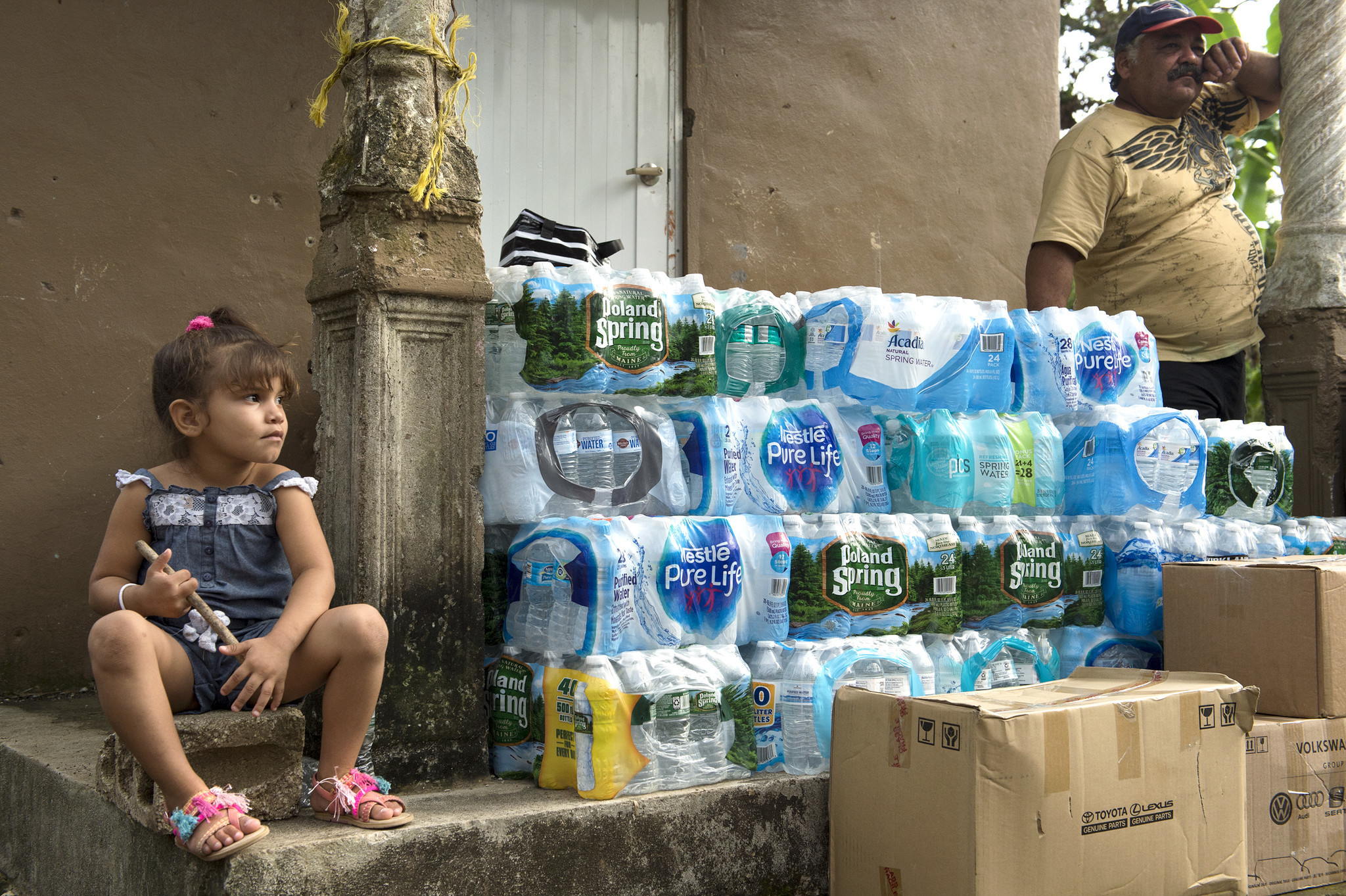 Aleanis Alvarado, 5, surveys the relief supplies that were brought to her neighborhood in Coamo, Puerto Rico by employees from the Hoffman Auto Group. At right is Jose Rivera Sanchez.