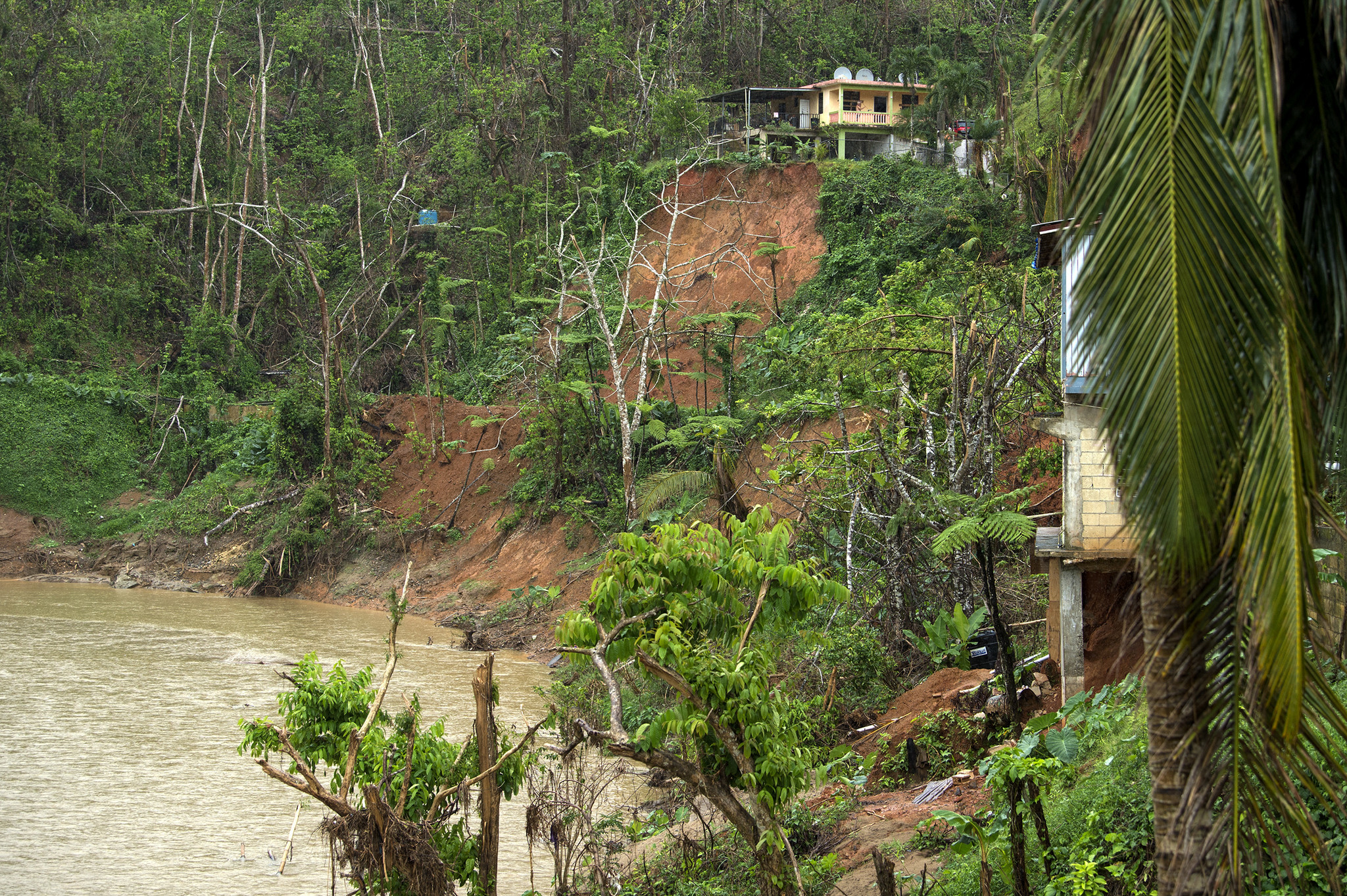 Homes on the banks of the Río Abajo neighborhood of Utuado, Puerto Rico show signs of mudslides and other damage after Hurricane Maria devastated the village. Samuel de Jesus' home sits near the edge of a tall slope, and he worries continuing rain might cause it to fall into the Río Viví below.