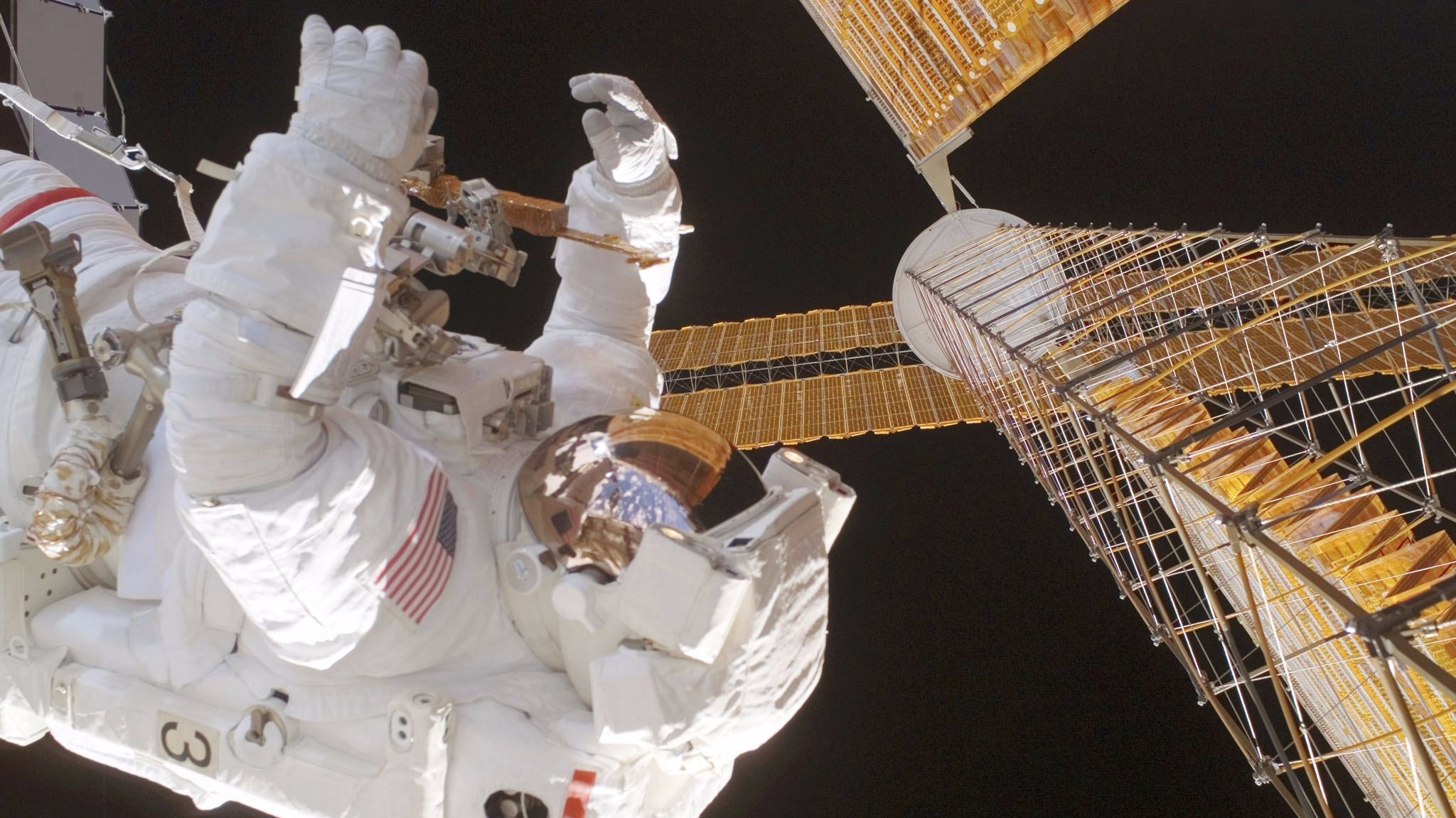 US space shuttle Discovery Mission Specialist US  Robert Curbeam inspects a balky solar array Dec. 18, 2006 on the International Space Station.
