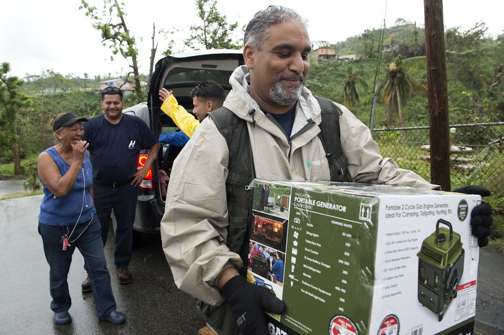 Mercedes Ramos smiles as Elliot Matos carries a generator to her taxi. The team gave Ramos the generator as a show of thanks for helping them navigate the damaged and confusing streets of Fajardo, a coastal city in the northeast corner of Puerto Rico. Matos learned that Ramos had been without electricity since Hurricane Maria struck and had been powering her husband