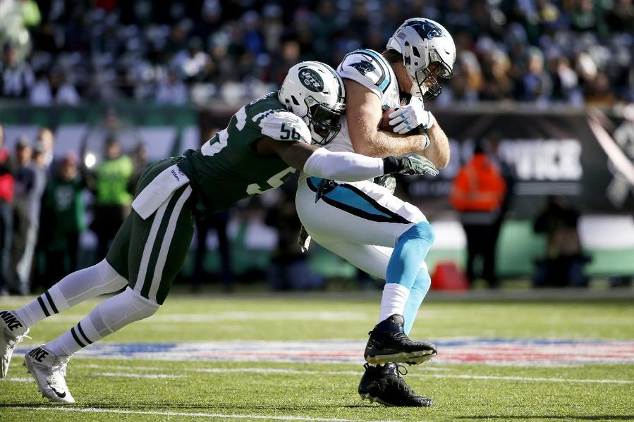Panthers tight end Greg Olsen is tackled by Jets linebacker Demario Davis during the first quarter of a game at MetLife Stadium. (Kathy Willens / Associated Press)