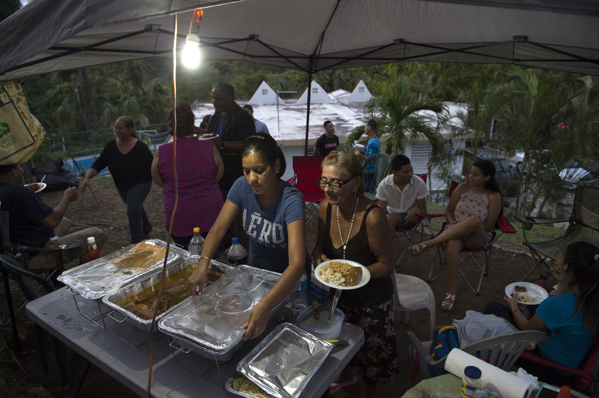 Doris Velasquez Santiago and her grandmother Monserrate Rivera (right) dish out food during a pig roast at their home in Coamo, Puerto Rico. The family threw the celebration to commemorate the completion of the mission carried out by Elliot Matos and his relief team. The family was able to enjoy the luxury of having electricity at the pig roast thanks to the generator brought to them from Connecticut.