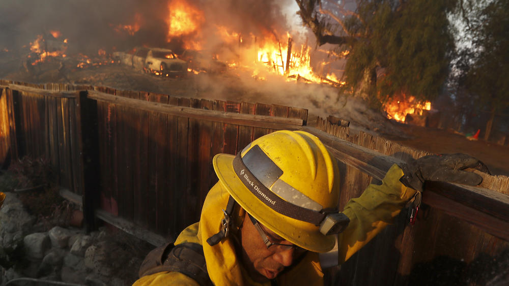 A firefighter monitors the Creek fire as it burns a house near the intersection of Johanna Avenue and Mc Broom Street in Shadow Hills