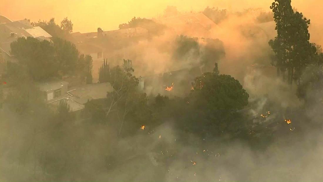Orange flames peek through heavy smoke from the Skirball fire in Bel-Air. (KTLA-TV)