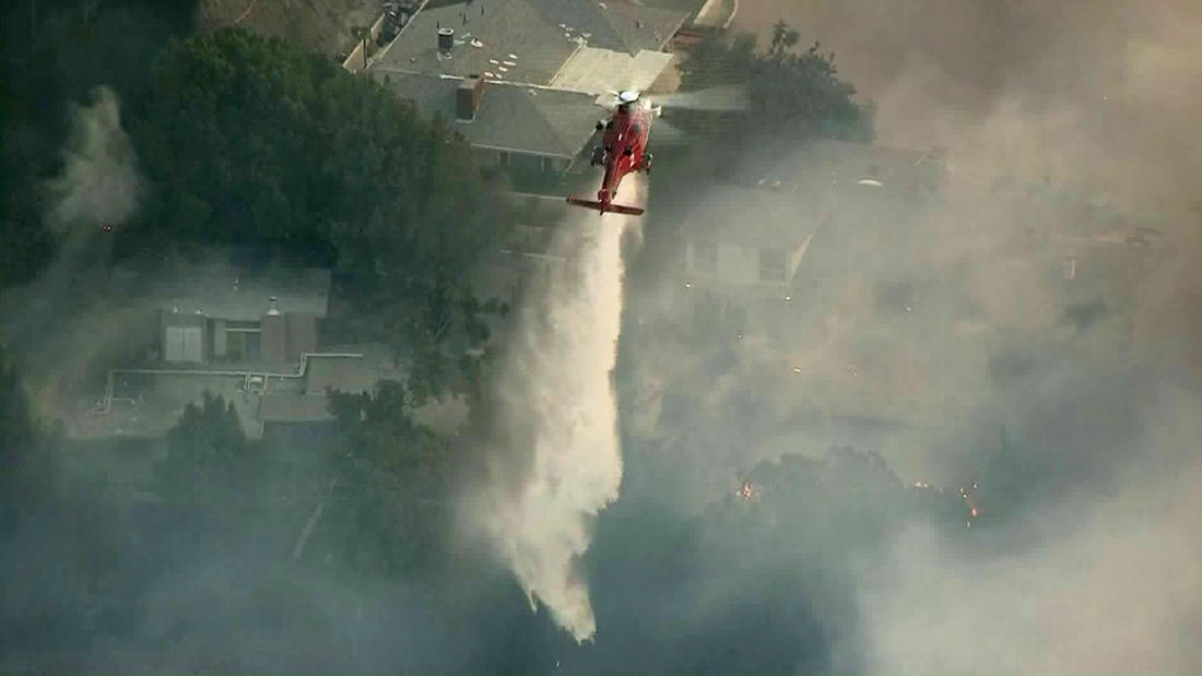 A helicopter makes a water dump on the Skirball fire burning Wednesday in the Bel-Air neighborhood. (KTLA-TV)