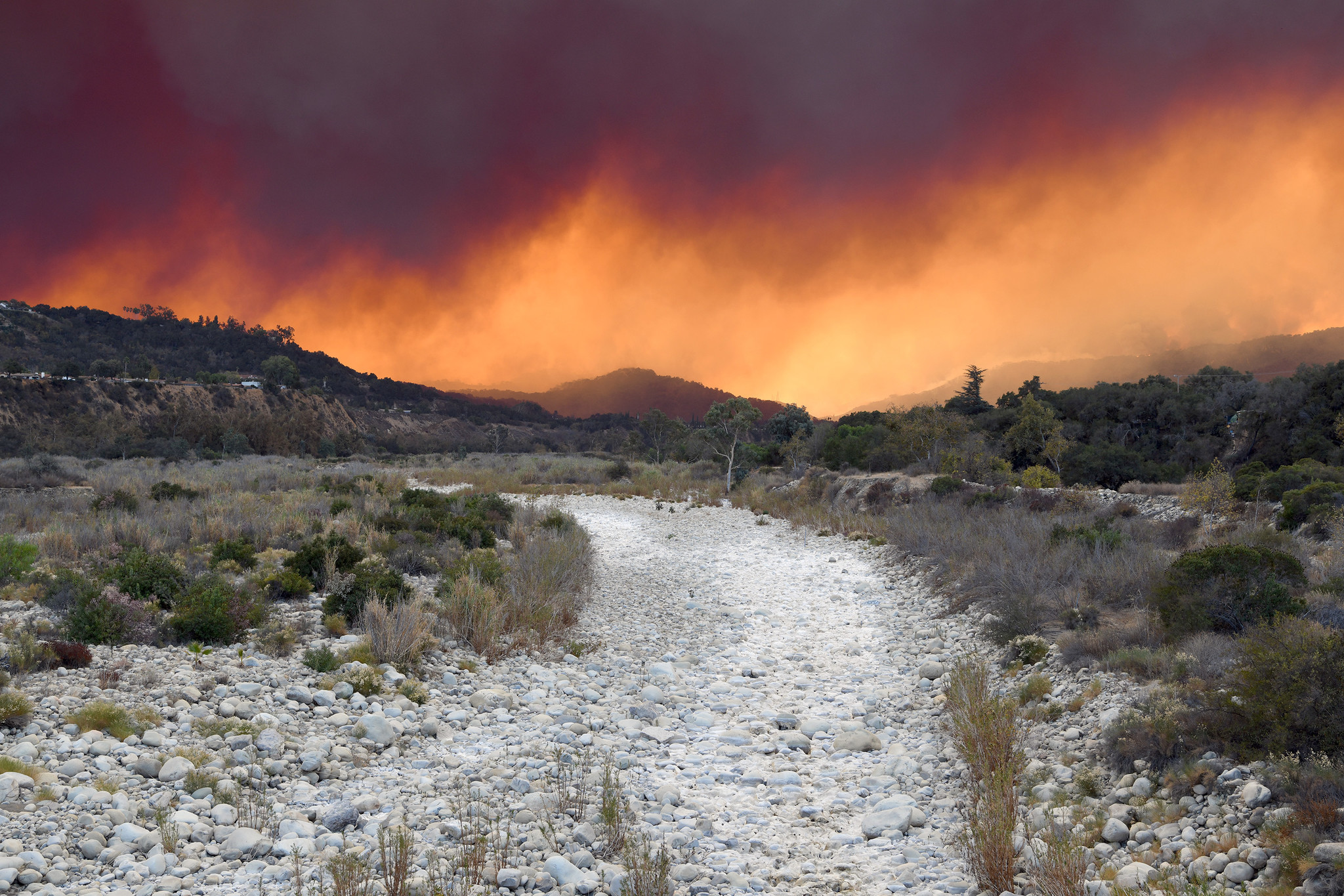 Smoke from the Thomas fire crosses over the dry Ventura River in Ojai. (Michael Owen Baker / For The Times)