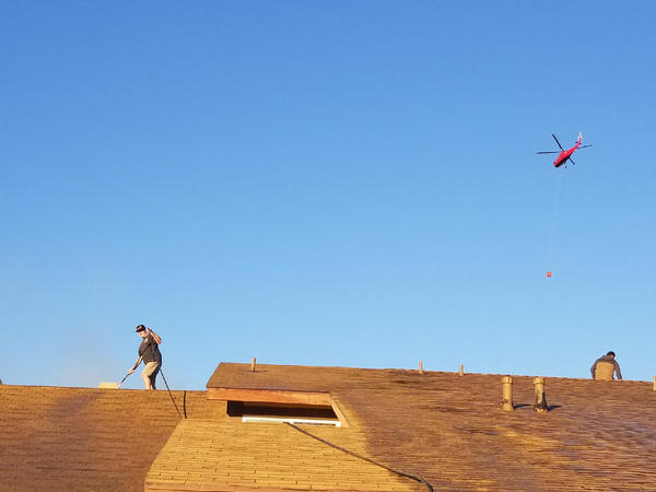 Colin Cantrall waters down his mother's roof with a garden hose. (Kristy Cantrall)