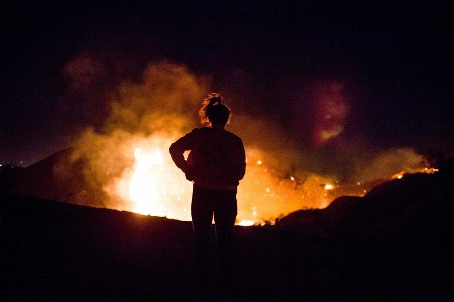 A resident watches as the Creek fire burns along a hillside near homes in Shadow Hills. (AFP/Getty Images)