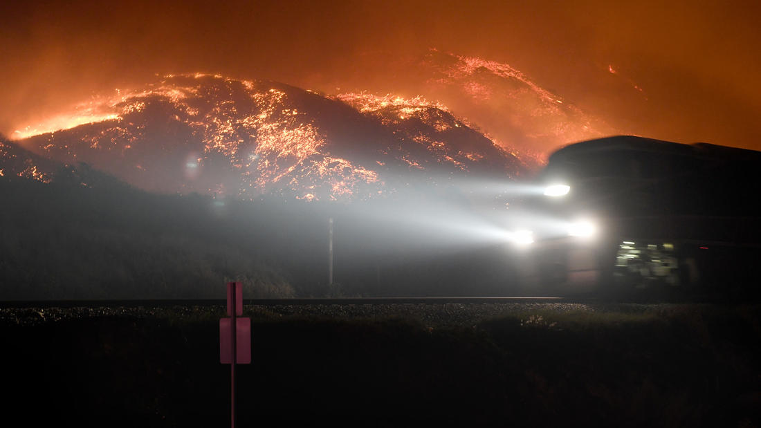 A train on the Rincon coast passes a burning hillside from the Thomas fire. (Michael Owen Baker / For the Times)