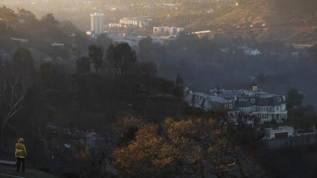 A firefighter monitors the scene over Bel-Air, where the Skirball fire has destroyed several homes. (Genaro Molina / Los Angeles Times)