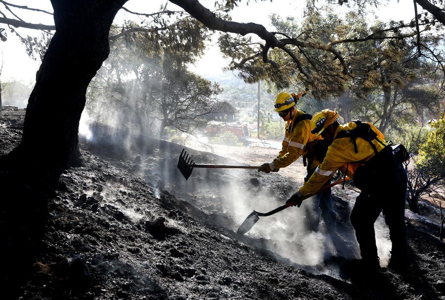 Firefighters work to put out a brush fire in Malibu in the hills above Pt. Dume. (Katie Falkenberg / Los Angeles Times)