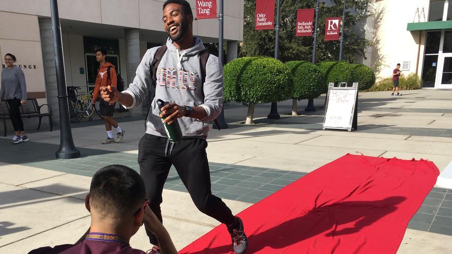 University of Redlands senior Marcus Garcia, left, takes a social media video of senior Afari La-Anyane walking down a DUDES runway event. (Rosanna Xia / Los Angeles Times)
